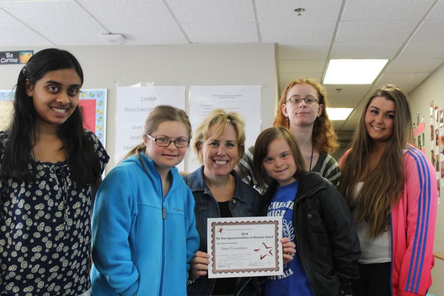 Mrs. Cosentino poses with her students and her award. She won the Rochester High School foundation Excellence in Education Award. Photo by Sarah Walwema