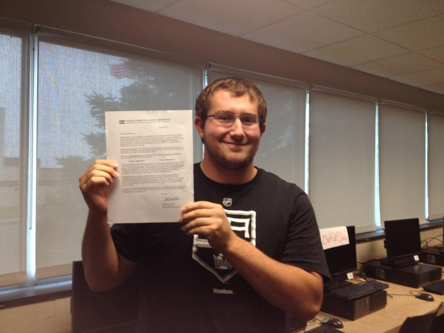 Markwort stands with the letter he received from the National Merit Scholarship Association.