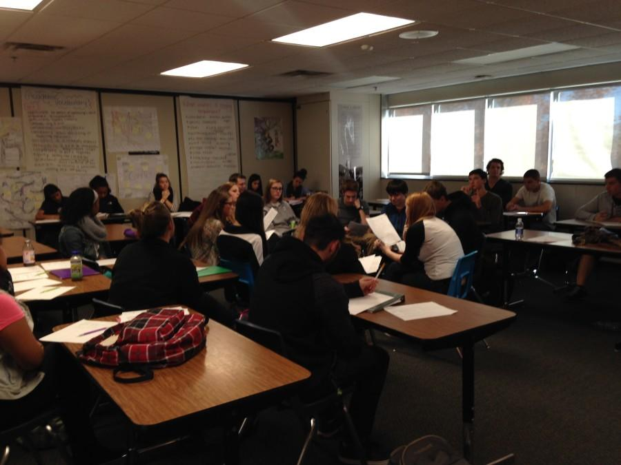 English teacher Ms. Wood teaches her class while the students discuss the novel they have been reading.