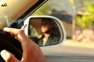 Adult smoking while driving.