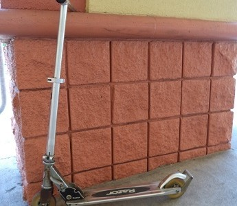 Tommy Hawes uses a kick scooter for transportation