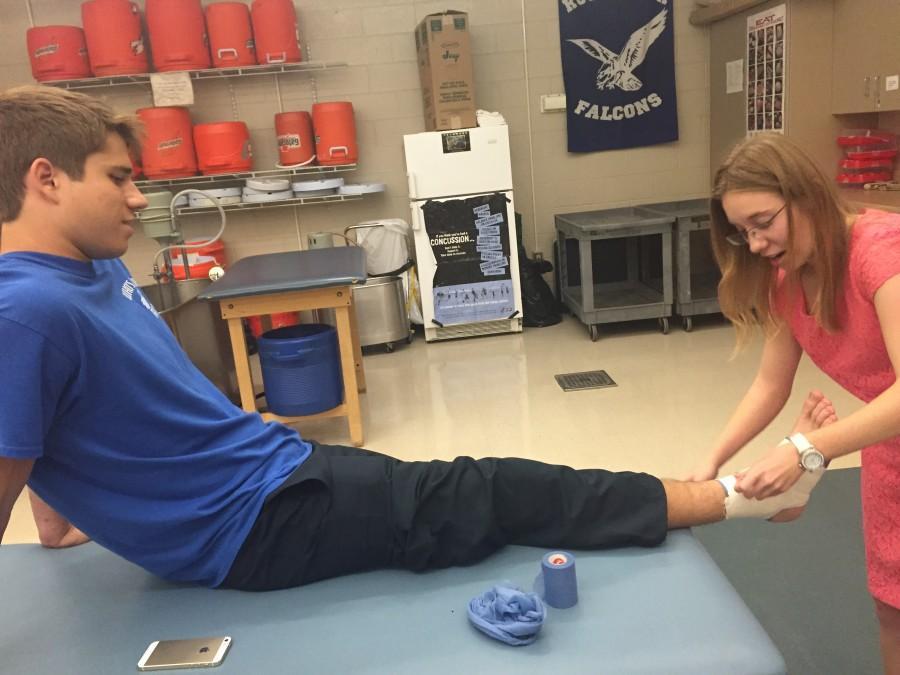 Junior+Elizabeth+West+wraps+senior+Alex+Grabowski%27s+ankle+after+school.