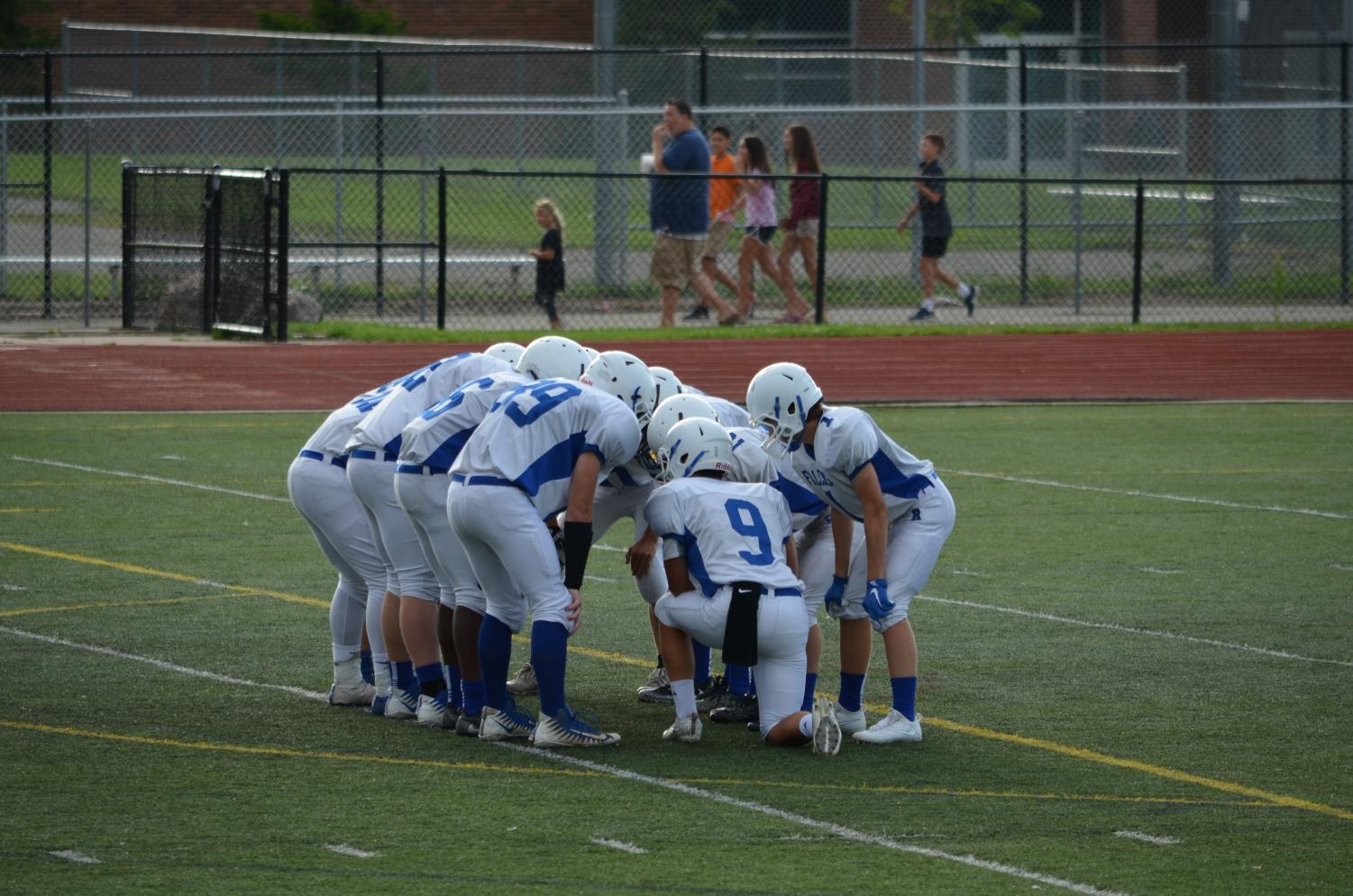 The JV football team in the huddle.