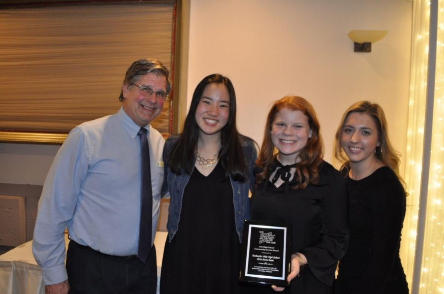 Captains Katherine Lee, Kendall Jordan, and Grace Forlines along with the Coach, Mr. Paul Karas, take a picture with the award