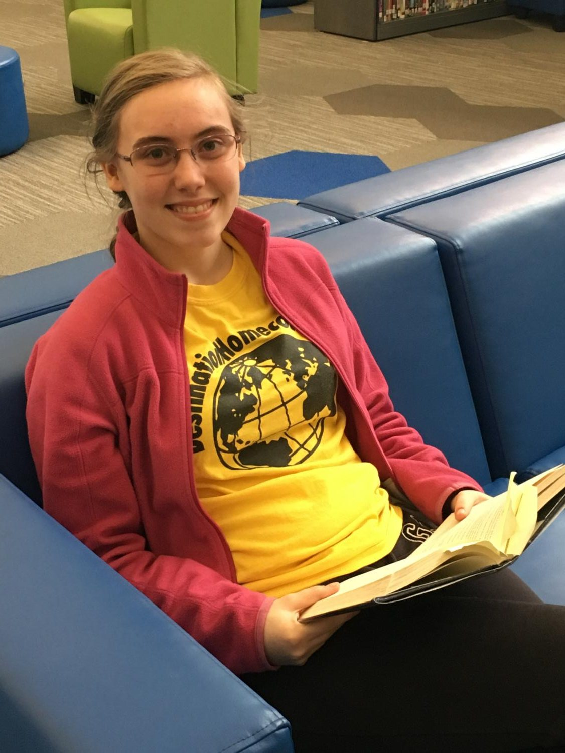 Freshman Sarah Vander Sluis enjoys a book in the RHS Media Center. Photo by Faith Schultz.