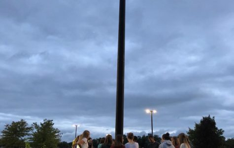 Reach members gather around the flag pole as they pray like they do towards the end of every meeting.
