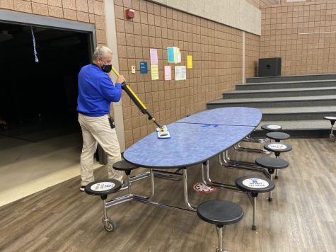 Staff works to ensure safety in the cafeteria by cleaning between lunches.